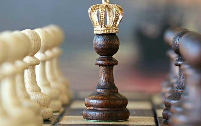 un pedone nero degli scacchi con una corona in testa, al centro di uno schieramento di pedoni semplici
