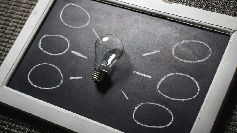 Una lampadina, al centro di una lavagnetta, sta a significare la possibilità di molte idee
